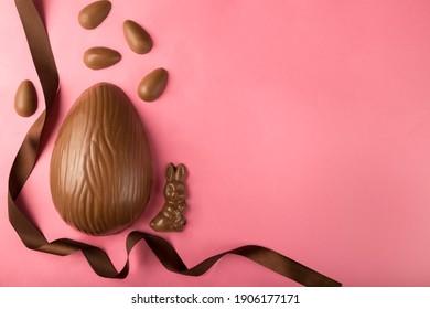 Ostern. Zusammensetzung mit Schokoladenostereiern auf rosa Hintergrund, Raum für Text.