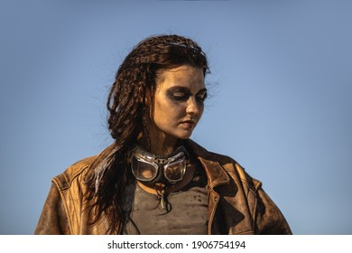 Post-apocalyptic woman portrait outdoors. Young slim girl warrior in shabby clothes standing in a confident pose looking down. Nuclear post-apocalypse time. Life after doomsday concept. Desert and