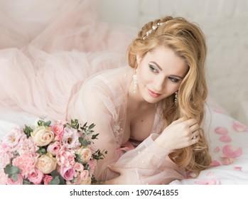 透明なペニョワールの長い髪の美しい少女の肖像画は、花の花束の横にあるベッドに横たわっています。花嫁の朝