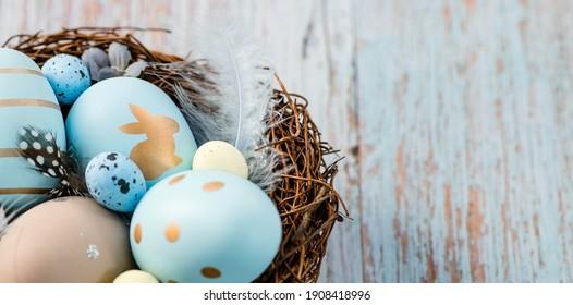 Banner.Ostereier, Federn in einem Nest auf einem blauen hölzernen Hintergrund. Das minimale Konzept von Ostern. Draufsicht. Eine Osterkarte mit einer Kopie des Platzes für den Text.