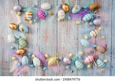 Banner. Osterrahmen mit Eiern und Federn auf einem blauen hölzernen Hintergrund. Das minimale Konzept von Ostern. Draufsicht. Eine Osterkarte mit einer Kopie des Platzes für den Text.