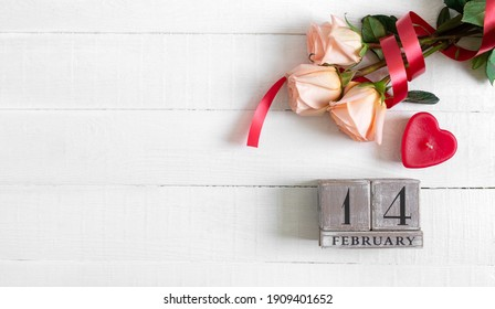 Wooden perpetual calendar on date February 14, candle-heart and a bouquet of roses. Concept Valentine's Day. Copy spase