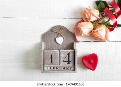 Wooden perpetual calendar on date February 14, candle-heart and a bouquet of roses. Concept Valentine's Day. Postcard.