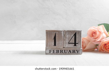 Wooden perpetual calendar on date February 14, bouquet of roses on a light background. Concept Valentine's Day. Copy space.