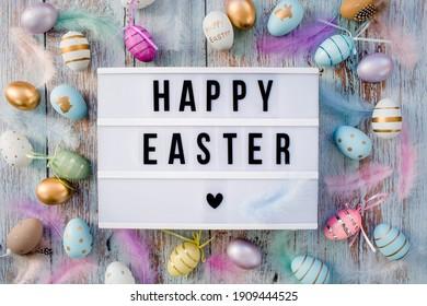 Stilvoller Textrahmen des Leuchtkastens mit der Aufschrift fröhliches Ostern. Überall sind rosa, blaue, weiße, goldene und gelbe Eier. Bunte Ostereier-Draufsicht von frohen Ostern. Copyspace.