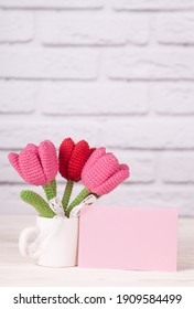 Gift for mother's day, international women's day, valentine's day. Needlework, handicraft, natural product. Crochet tulips in a cup on a light brick background. DIY