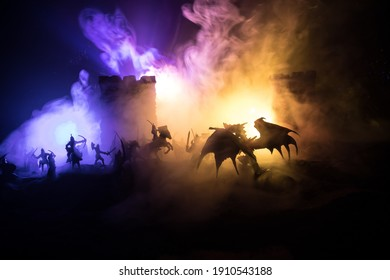 Fantasy-Kampfszene mit Drachen, die nachts eine mittelalterliche Burg angreifen. Kampf zwischen Drachen und heldenhaften Soldaten. Kreative Tischdekoration. Selektiver Fokus