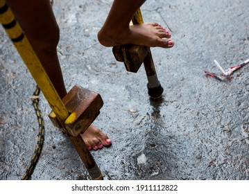 Kids playing with wooden leg in the rain at a vacation program in a neighbourhood in the city of Mariana, Minas Gerais, Brasil.