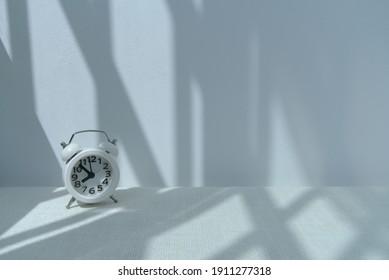 テーブルの上の1つのビンテージ目覚まし時計。壁の日光の下での窓の影のパターン