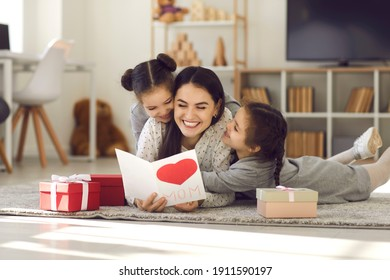 Wij houden van u. Lachende jonge vrouw cadeautjes krijgen van kinderen. Twee schattige tweelingdochters die moeder handgemaakte wenskaart geven. Mijn lieve kinderen die op de vloer liggen, mama knuffelen en haar gelukkige moederdag wensen