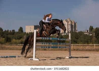 女の子は手綱なしで高い障壁を越えて馬にジャンプします。危険なスポーツ。新鮮な空気の中で通りをジャンプする障害飛越競技。セレクティブフォーカス、ノイズ効果のある画像