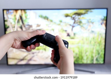 Gamepad in female hands closeup on TV screen background, gaming addiction concept. Girl gamer playing video games with joystick