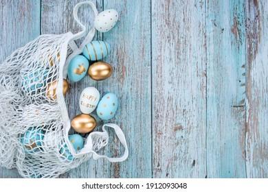 Gold, Schwarz, Weiß, Blau Ostereier in einer Schnur Tasche auf einem blauen hölzernen Hintergrund. Geometrie. Das minimale Konzept von Ostern. Draufsicht. Eine Osterkarte mit einer Kopie des Platzes für den Text.