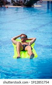 若い男が黄色の膨脹可能なマットレスの上でプールで入浴します。休暇中は明るい太陽の下でリラックスしてください。幸せな成功した男
