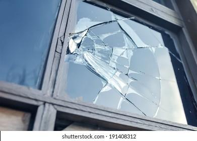 青い空を反映して壊れたガラス窓