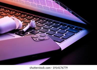 Ein Laptop, der im Dunkeln halb geschlossen war, mit einem Telefon und leuchtenden kabellosen Kopfhörern