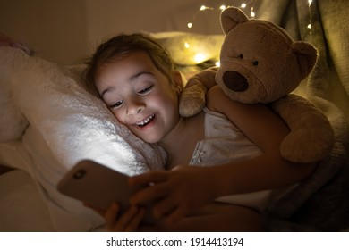 Little girl watching smartphone in bed, kid using phone and play game, child using mobile, addicted game and cartoon.