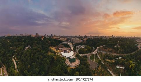 空からのキエフのパノラマビュー。人々の友情のアーチと夏のキエフに沈む夕日。ドローンで撮影。航空写真