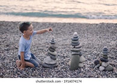 幸せな少年は海岸に石のケアンを建てます。子供とのビーチゲーム。子供との休暇の夕方の余暇。バランス開発ビルディングファンタジー。子供時代。楽しい喜び。オーシャントラウェル