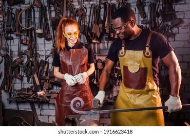 愛のカップル赤毛生姜若いヨーロッパの女性と革のエプロンを身に着けているアフリカ系アメリカ人の男性鍛冶屋のワークショップ。小さな家族の国際的なビジネスコンセプト
