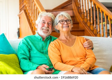 Couple of two happy seniors sitting on the sofa at home watching the tv and fighting for the remote control of the TV