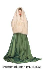 かなり長い緑のスカートと白い背景で隔離の毛皮のマントで長い巻き毛を持つ美しいエレガントな若いティーンエイジャーの女の子のファッション写真。ロシアの美しさ