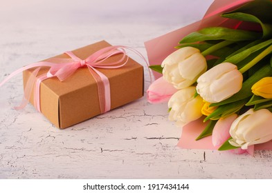 Holiday banner. Bouquet of pink and white tulips with gift box on light old  background. Mothers day, Valentines Day, Birthday celebration concept. Copy space for text, top view