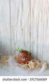 Drawing of an easter teddy bear on an egg, cute faces, teddy bear in a spring wreath on a wooden natural background, decor for the holiday