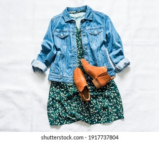 Women's clothing for spring, summer, autumn - denim jacket oversize, floral dress, suede chelsea boots on a light background, top view