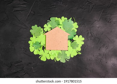 黒の背景に四つ葉のクローバーと幸運な家のシンボル。テキスト用のスペースをコピーします。聖パトリックの日のコンセプト。