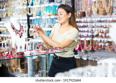ブティックでファッションジュエリーを買い物し、指輪を探してデモンストレーションする若い女性の肖像画