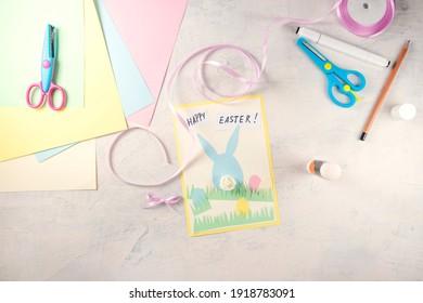 Schritt für Schritt Anleitung: wie man Karte Happy Easter macht. DIY Kreativität. Schritt 7 Kleben Sie Notizen mit den Worten HAPPY EASTER und binden Sie eine Schleife. Handgemachtes Osterhandwerk. Draufsicht