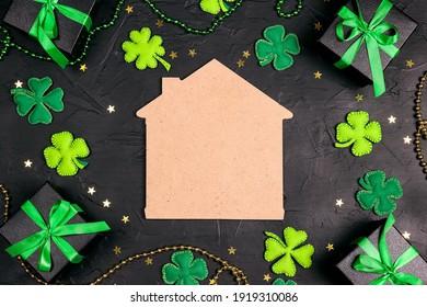 Glückliches Heimsymbol, umgeben von Geschenken, vierblättrigem Kleeblatt und Sternen auf schwarzem Hintergrund. Kopieren Sie Platz für Text. St.Patrick's Day Konzept.