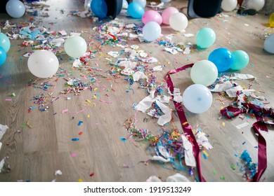 Draufsicht des Bodens mit nach einer Partyfeier mit leeren blauen Flaschen, Weinglas und Partydekorationen, unordentlichem Wohnzimmerinnenraum, After-Party-Chaos, Geburtstag