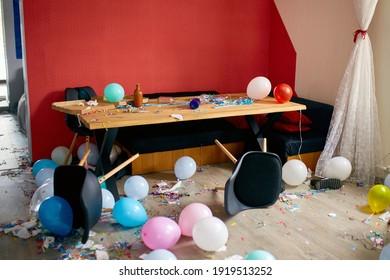 Nach dem Party-Chaos, unordentlich im Wohnzimmer zu Hause, Tisch mit Pizza und Champagnergläsern, bedeckt mit Konfetti und Ballons, Stuhl auf dem Boden am Morgen nach der Partyfeier.