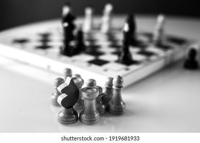 Figuras de ajedrez blancas y negras con tablero en mesa blanca en casa. Para hacer en casa en cuarentena de coronavirus. Juegos en casa. Educación para niños. Juegos intelectuales. Juegos mentales. Zona de confort para juego de mesa