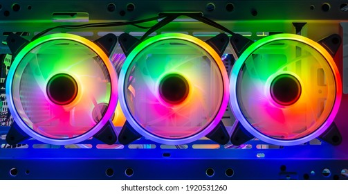 three colorful bright rainbow led rgb pc fan air case cooler in white desktop computer chassis. gaming modding water cooling and technology concept background