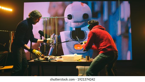 View of male sound designers recording clinking of chains and drill buzz while creating audio for 3D cartoon about robot