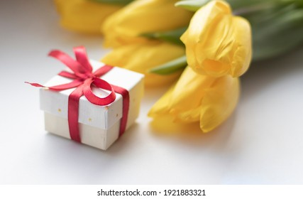 sunlight on yellow tulips near gift box on white, mothers day concept