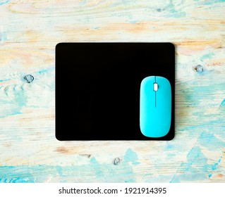 Black pad and blue computer mouse set on wooden colorful background. Modern office mockup for business logo or presentation.