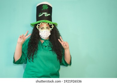 Woman with hat and luminous shamrock glasses and mask by Covid 19 celebrating St. Patrick´s Day. With green background.
