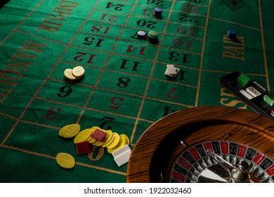 Ruleta en legno isolata sopra un tavolo da gioco verde con fiches colorate