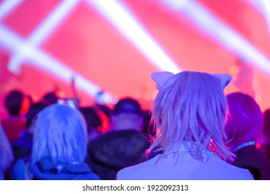 Pink hair teenage girl with anime cat ear partying and cheering at rock concert in front of stage of nightclub - back view. Bright colorful stage lighting. Nightlife and entertainment concept
