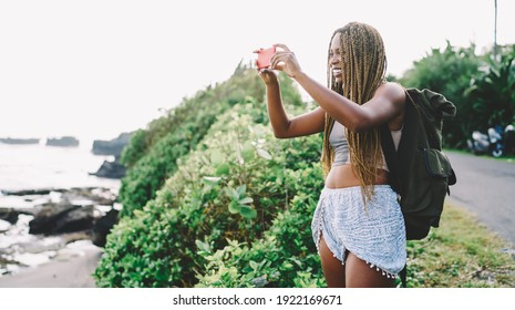 Cheerful African American traveller with backpack making photos of tropical nature environment using smartphone application and internet, joyful tourist photographing scenery view during summer trip