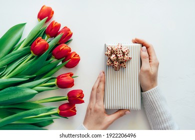 Top view of hands holding a wrapped elegant gift on a white background. Nearby lies a bouquet of red fresh tulips. Festive spring concept. Copy space for text.
