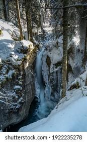 Bach im Tal im Wintergewand, schneebedeckt und mit Eiszapfen im frisch schneebedeckten Wald. Bach mit Wasserfall zwischen schneebedeckten Bäumen. Tal im Bregenzer Wald im Winterwunderland