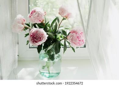 Una vista de un ramo de peonías rosas de pie en un jarrón en la ventana. Fondo del concepto, flores, vacaciones