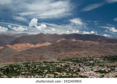 アルティプラノの風景。アルゼンチン、フフイのウマウアカ渓谷のふもとにあるティルカラ村。雲と美しい空の下で色とりどりの山々や町の建物のパノラマビュー。