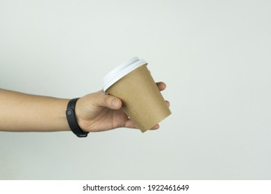 A girl's hand grabs the take-away paper cup that is used for coffee. This photo is suitable for use as a mockup to put your logo or design