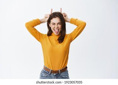 Ze is een rebel. Mooie jonge vrouw met tong en vinger duivel hoorns op hoofd, koppig, brutaal knipogen naar de camera, staande tegen een witte achtergrond.